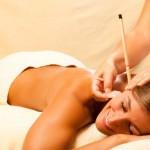 Frau mit Ohrenkerze und Edelstein Massage